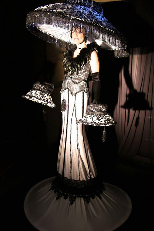 Erté style costume with lit-from-within shade, on stilts.