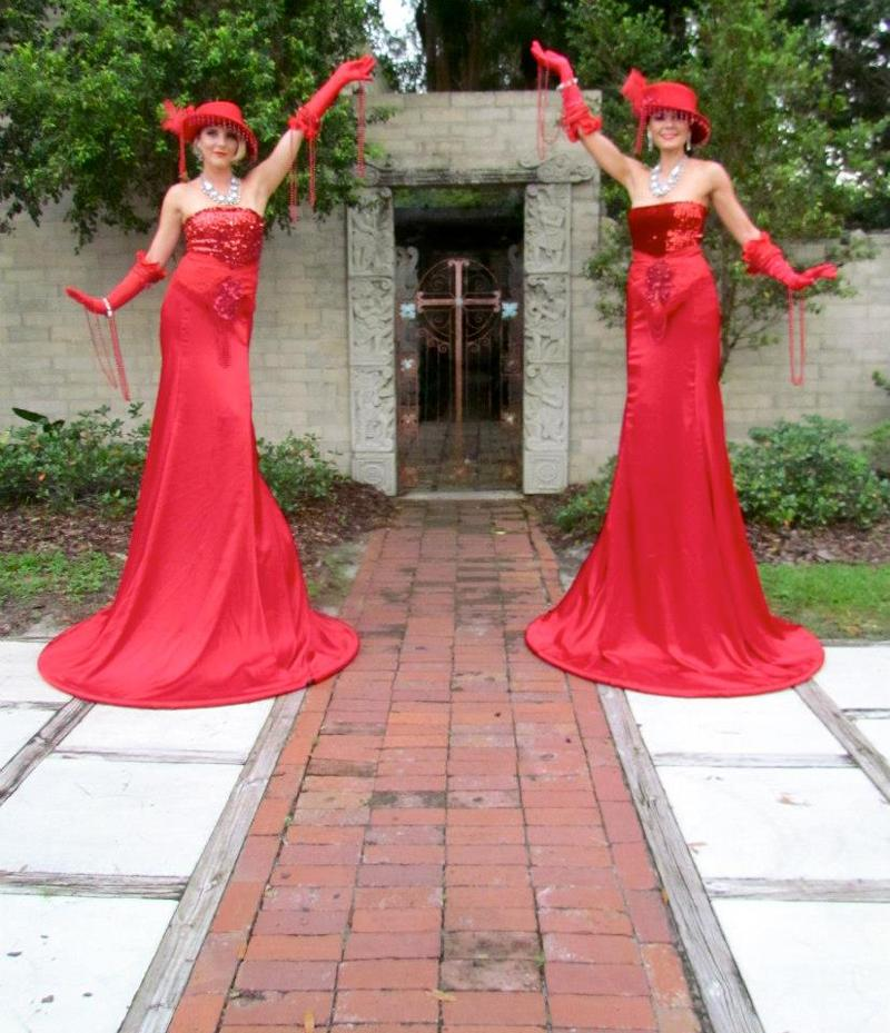 Red gowned stilt greeters - Florida